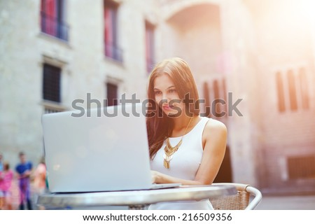 Beautiful brunette girl looking to the pc laptop screen, young attractive woman typing something on a laptop keyboard, smiling young woman is using a laptop outdoors, dating and technology concept - stock photo