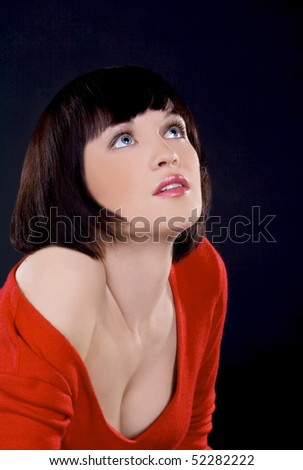 Beautiful brunette girl posing in studio on dark background