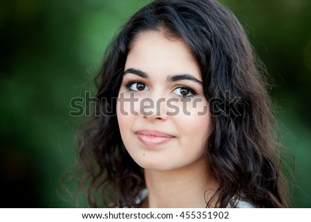 Beautiful brunette girl relaxing in the park wiht many plants of background - stock photo