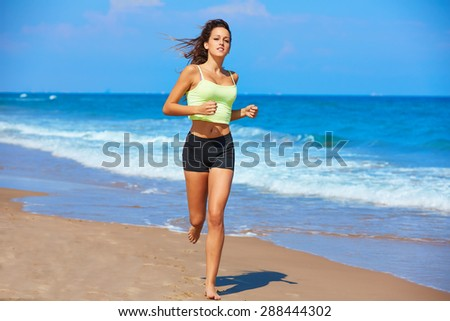 Beautiful brunette girl running in the beach at summer vacations - stock photo