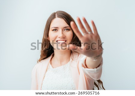 beautiful brunette girl shows stop - stock photo