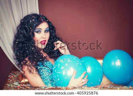 Beautiful brunette girl sitting in a bathtub filled with blue balloons and flirtatious looks, cocktail party, bachelorette party - stock photo