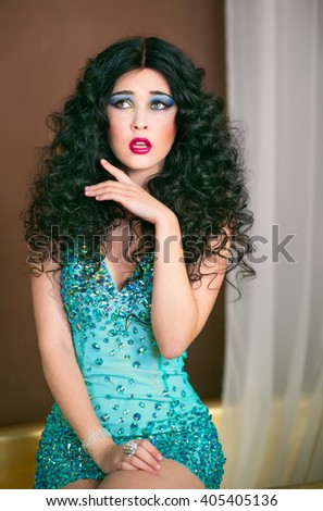 Beautiful brunette girl sitting on the edge of the bath in bright turquoise short dress, cocktail party, bachelorette party - stock photo