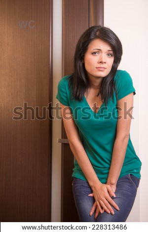 beautiful brunette girl standing at toilet door. pretty black haired woman wants to pee - stock photo