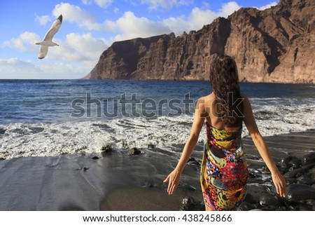 Beautiful brunette girl standing on the beach of Los Gigantes in Tenerife with black sand, mountains and flying seagull - stock photo