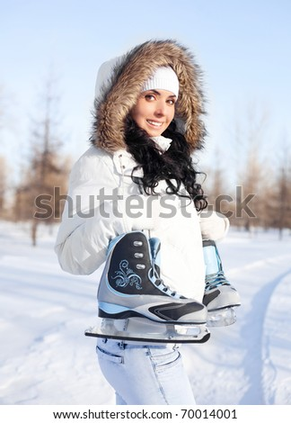beautiful brunette girl wearing warm winter clothes going to ice skate - stock photo
