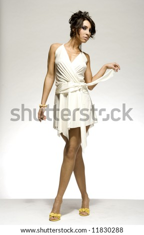 beautiful brunette girl wearing white dress and yellow shoes on light background - stock photo