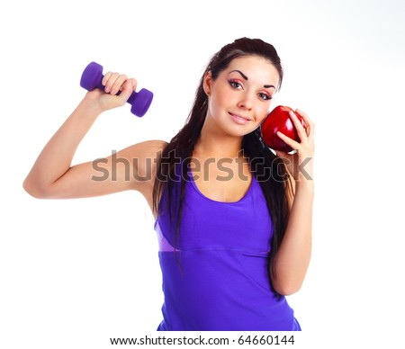 beautiful brunette girl with a dumbbell and an apple