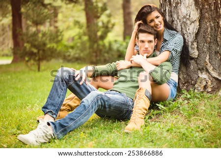 Beautiful brunette girl with a handsome guy, sitting on the grass in the park.