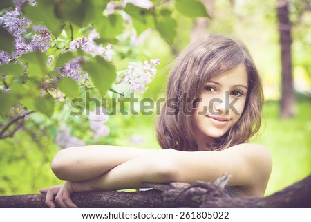 Beautiful brunette girl with a lilac flowers  relaxing and enjoying life in nature. Outdoor shot. Copyspace - stock photo