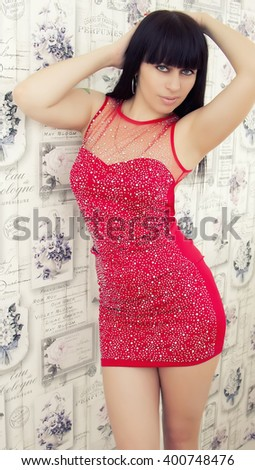 Beautiful brunette girl with blue eyes in a red dress - stock photo