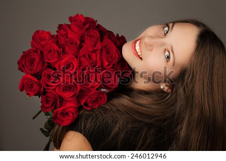 Beautiful brunette girl with bouquet of flowers - stock photo