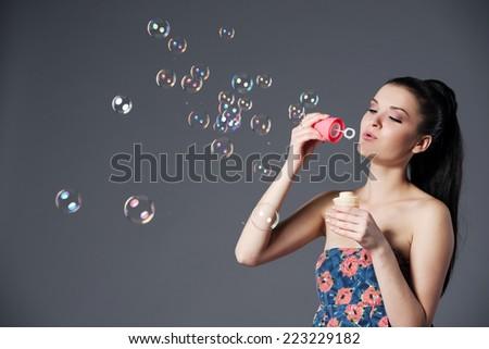 beautiful brunette girl with bubbles studio shot - stock photo