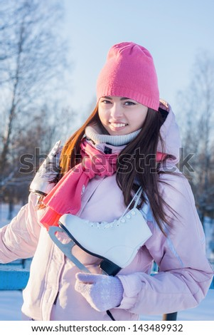 beautiful brunette girl with ice skate outdoor - stock photo