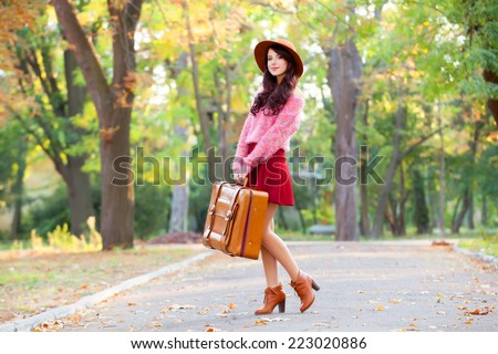 Beautiful brunette girl with suitcase in the park. - stock photo