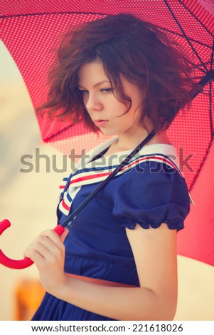 Beautiful brunette girl with umbrella on the countryside road. - stock photo