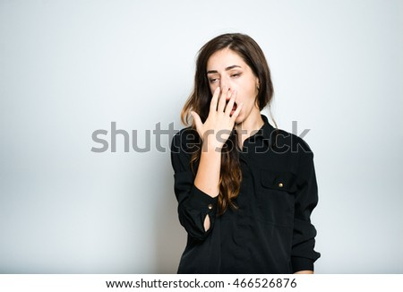 beautiful brunette girl yawns in black, isolated on white background