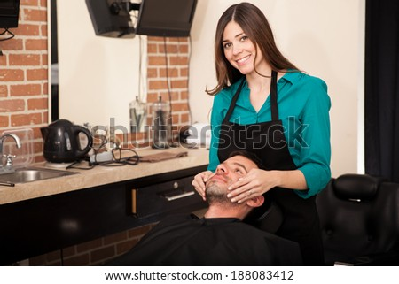 Beautiful brunette giving a face massage to a client before shaving his beard - stock photo