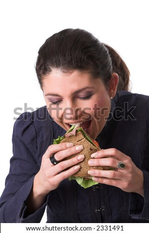 Beautiful brunette holding a big sandwich in her hand with salad and roastbeef and taking a big bite - stock photo