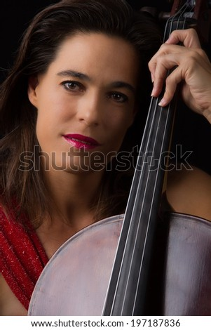 Beautiful brunette holding a cello with selective light in red dress - stock photo