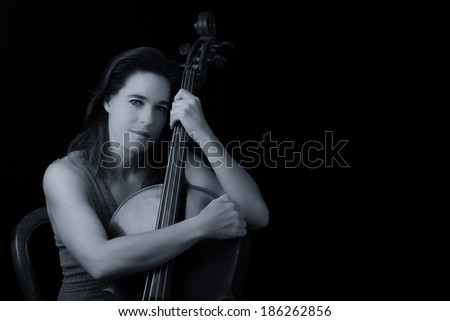 Beautiful brunette holding a cello with selective light in red dress artistic conversion