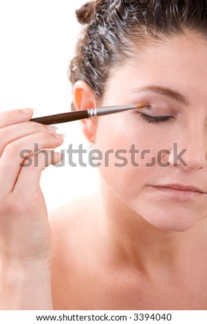 Beautiful brunette holding a makeup brush in her hand applying eyeshadow