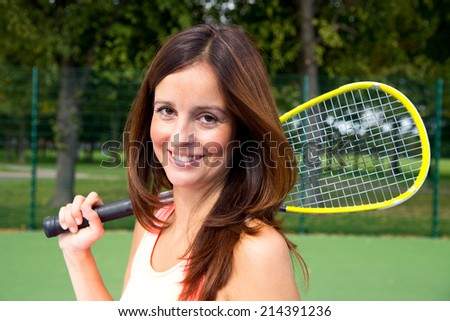 beautiful brunette holding a squash racket. - stock photo