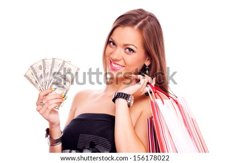 Beautiful brunette holding American hundred Dollar bills and shopping bags over shoulder, isolated on white - stock photo