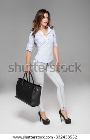 Beautiful brunette holding bag - stock photo