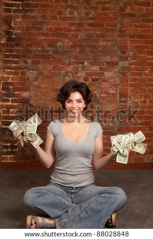 Beautiful brunette holding dollars bills - stock photo