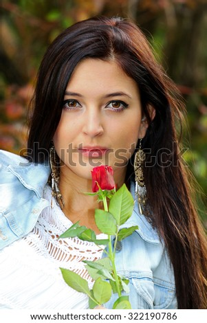 Beautiful brunette holding red rose. - stock photo