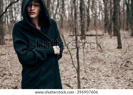 Beautiful brunette in a black cloak standing in the woods with closed eyes