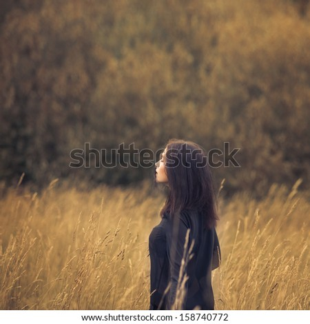 beautiful brunette in a field - stock photo