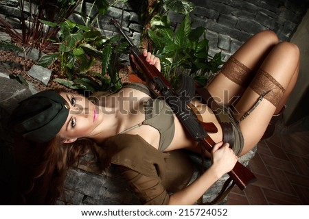 Beautiful brunette in a green underwear, military jacket, military cap and with a sub-machine gun, lies in a interior, glamour photography