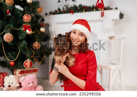 Beautiful brunette in a red dress and Santa Claus hat holding her little dog and posing against a background of Christmas decorations - stock photo