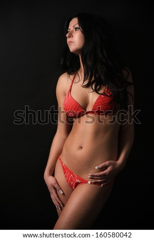 Beautiful brunette in a red swimsuit posing on the black background, in the studio, glamour photography - stock photo