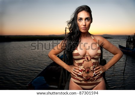 Beautiful brunette in a swimsuit at the harbor at sunset - stock photo