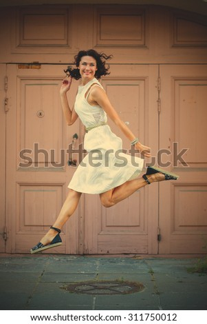 beautiful brunette in a white dress jumped on the background of old doors. instagram image filter retro style - stock photo