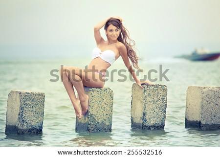 Beautiful brunette in bikini on the beach - stock photo