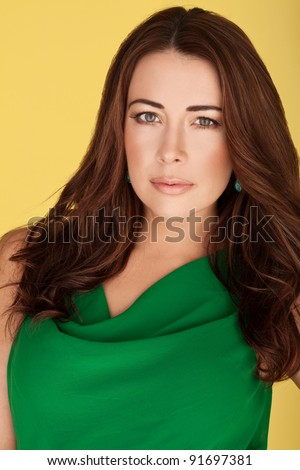 Beautiful Brunette In Green Dress. Beautiful brunette with subtle make-up gazing directly at the camera in an emerald green dress on yellow studio background. - stock photo