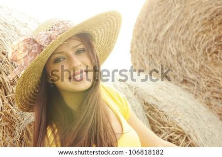 Beautiful brunette in sun hat on Haystack background - stock photo