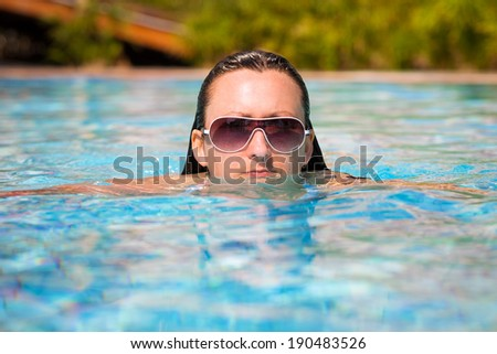 Beautiful brunette in sunglasses at the swimming pool