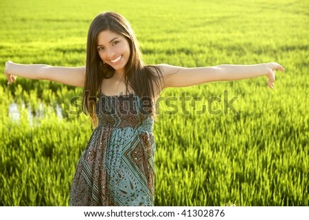 Beautiful brunette indian young woman in the green rice fields meadow - stock photo