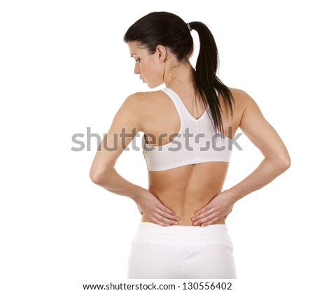 beautiful brunette is having a pain in her back - stock photo
