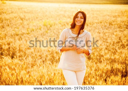 Beautiful brunette lady in wheat field at sunset - stock photo