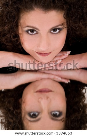 Beautiful brunette leaning on her hands with her reflection in a mirror - stock photo