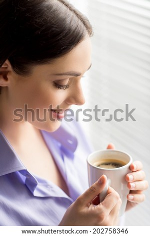 beautiful brunette looking at cup of coffee. closeup of young woman standing near window