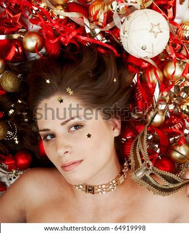 Beautiful brunette lying among Christmas decoration - stock photo