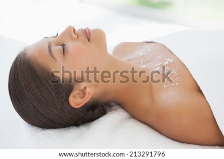 Beautiful brunette lying on massage table with salt scrub on chest at the health spa - stock photo