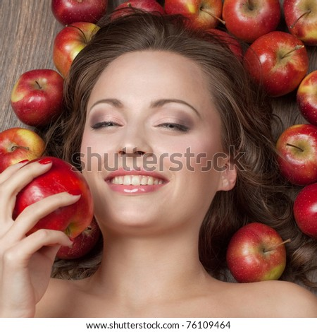 Beautiful brunette lying on the floor surrounded by apples and keeps one in his hand